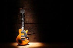 Music concept.Electric guitar standing near wooden wall under beam of light